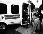 Helping client onto van, Providence ElderPlace, Seattle, Washington, 1990s